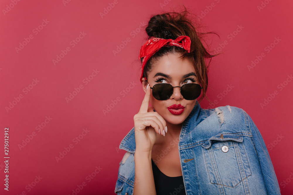 Fototapety, obrazy: Adorable pensive girl in sunglasses posing on claret background. Graceful black-haired female model in vintage attire thinking about something.
