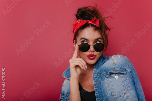 Adorable pensive girl in sunglasses posing on claret background. Graceful black-haired female model in vintage attire thinking about something.