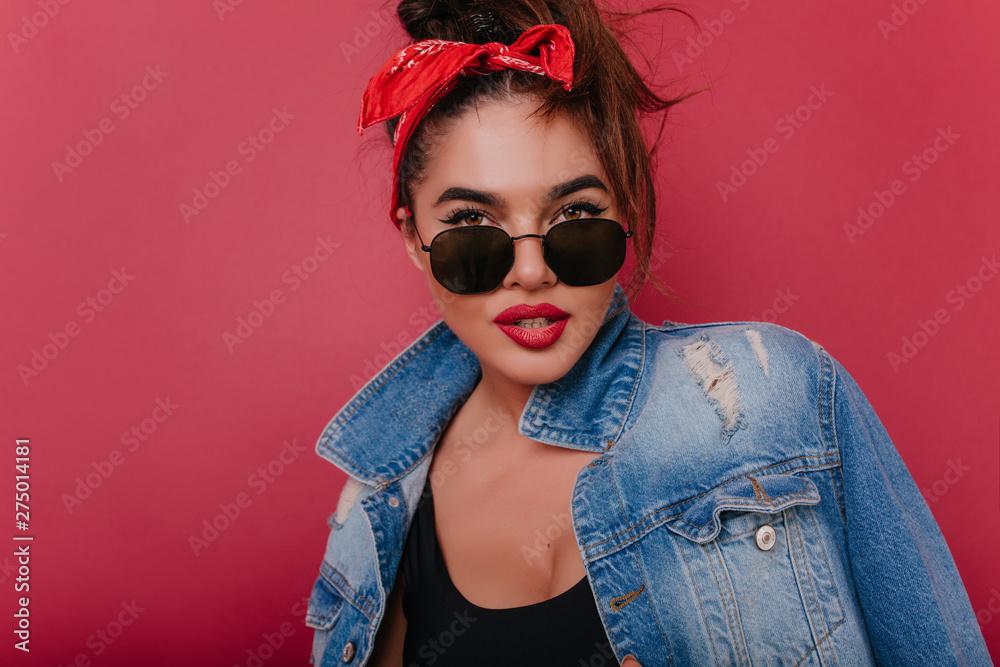 Fototapety, obrazy: Enchanting brown-eyed girl with retro hairstyle posing on claret background. Indoor close-up photo of interested brunette female model in stylish denim jacket.