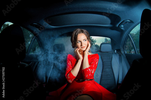 Stylish girl in a red dress posing in the back seat of a car