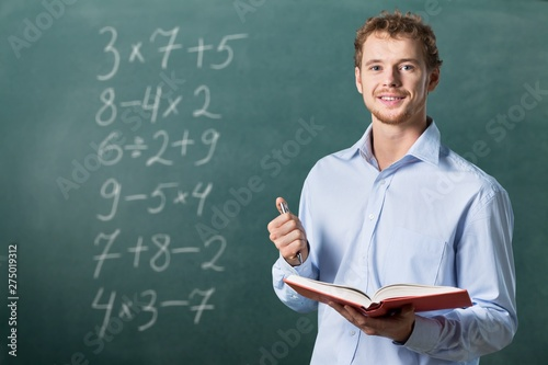 Foto Young male teacher   standing with book