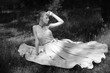 canvas print picture - blonde in white dress sitting on the grass,