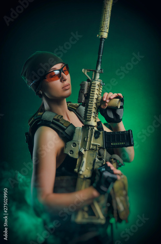 Fotografie, Obraz the girl in military special clothes posing with a gun in his hands on a dark ba