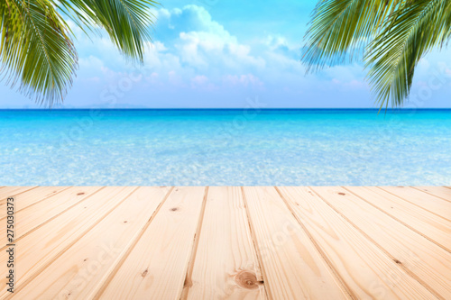 Foto auf Gartenposter Palms Wooden floor or plank on sand beach in summer. For product display.Calm Sea and Blue Sky Background.