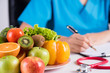 Healthy lifestyle, food and nutrition concept. Close up of fresh vegetables and fruits with stethoscope lying on doctor's desk.