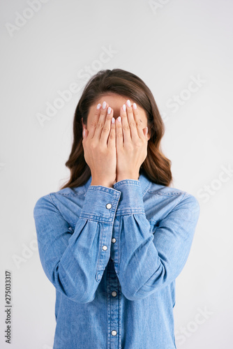 Poster Individuel Woman covering her face with her hands at studio shot