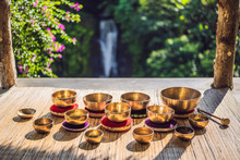Tibetan Singing Bowls On A Straw Mat Against A Waterfall