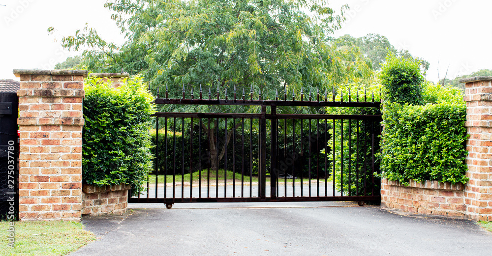 Fototapeta Black metal driveway property entrance gates set in brick fence with garden shrubs and trees in background