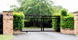 Black metal driveway property entrance gates set in brick fence with garden shrubs and trees in background