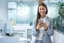Young Businesswoman Using Mobile Phone In Modern Office.