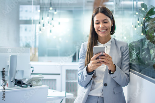 Fotomural  Young businesswoman using mobile phone in modern office.