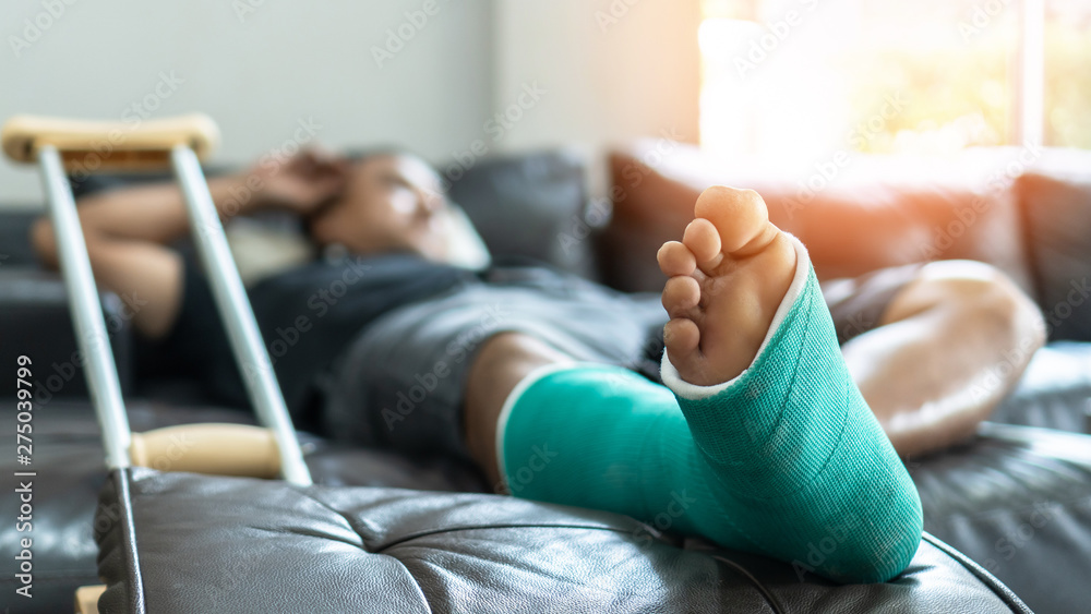 Fototapety, obrazy: Bone fracture foot and leg on male patient with splint cast and crutches during surgery rehabilitation and orthopaedic recovery staying at home