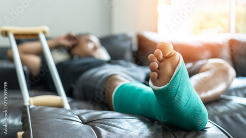 Fotografia Bone fracture foot and leg on male patient with splint cast and crutches during