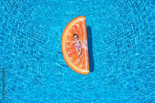 Süßes Baby mit Sonnenbrille und Badeanzug liegt auf einer Orangenscheiben Luftma Wallpaper Mural