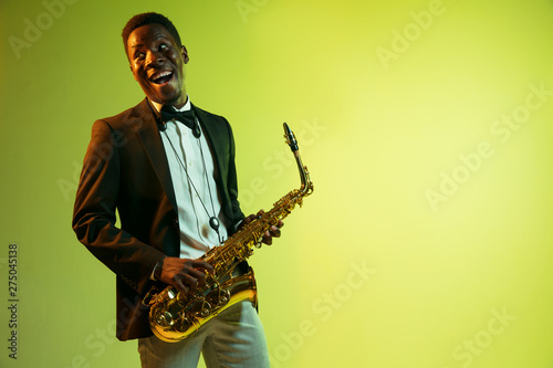Young african-american jazz musician playing the saxophone on gradient yellow-green studio background. Concept of music, hobby, festival. Joyful attractive guy improvising. Colorful portrait of artist - 275045138