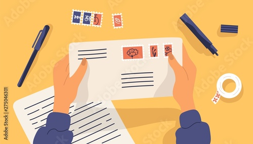 Foto Hands holding envelope with stamps surrounded by stationery