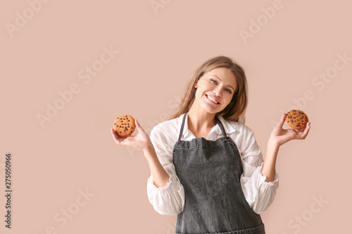 Obraz na plátne Happy female baker with tasty cookies on color background