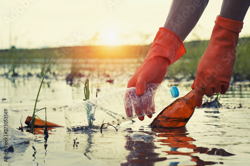 Fotografie, Tablou woman hand picking up garbage plastic for cleaning at river with sunset