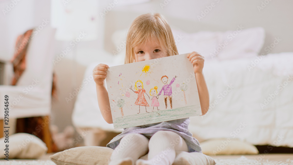 Fototapeta Cute Young Girl Sitting on Pillows and Shows Drawing of Her Family and Hides Behind It. Sunny Living Room.