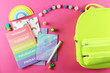 Hipster neon green textile backpack, surrounded with school supplies. Back to school concept. Lots of different stationery items on colorful background. Close up, copy space, flat lay, top view.
