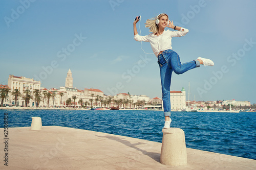 Holiday and music. Happy young woman with earphones and smartphone dancing on seafront promenade embankment. - 275061958