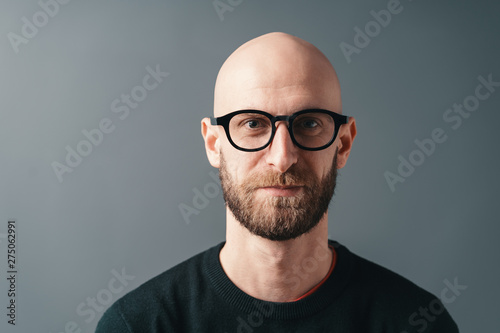 Fototapeta Young smiling man with beard and glasses on gray studio background