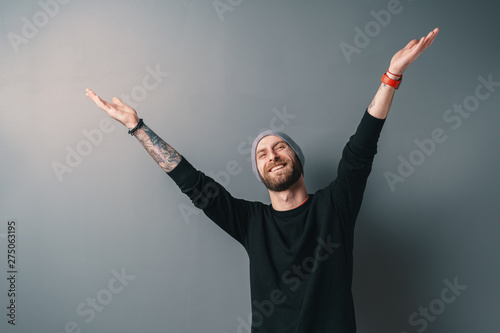 Photo  Man with glasses gesturing and smiling while standing against grey background