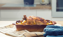 Roasted Whole Chicken With Potatoes In Baking Dish. Tasty Food At Home On The Kitchen Counter