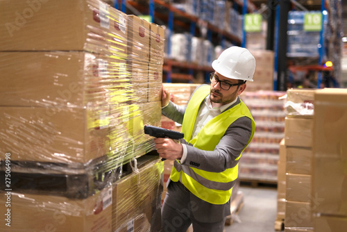 Obraz Working at warehouse. Male warehouse worker using bar code scanner to analyze newly arrived goods for further placement in storage department. Employee organizing goods distribution to the market. - fototapety do salonu