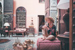Leinwanddruck Bild - Traveling by Morocco. Happy young woman in hat relaxing in traditional riad interior in medina.
