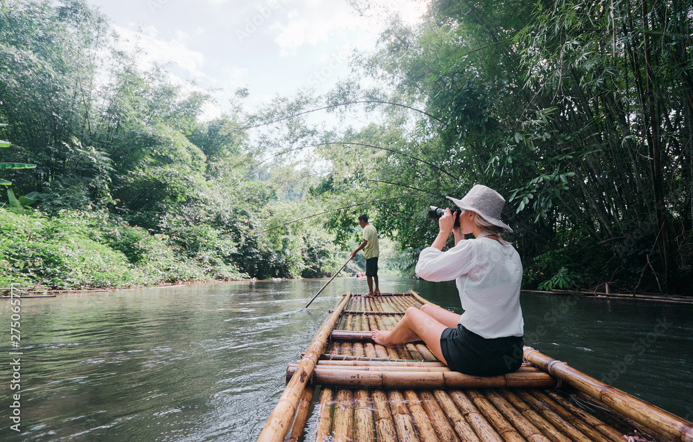 Fototapety, obrazy: Traveling by Thailand. Pretty young woman taking photo sailing jungle river on traditional bamboo raft.