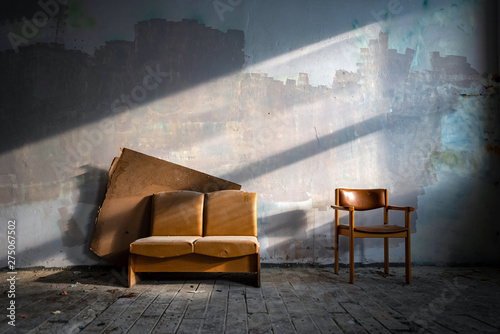 Old leather couch in abandoned factory building side lit by sun Wallpaper Mural