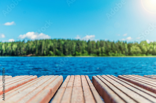 Fotografija Wooden timber of a rural mooring on a lake in the middle of the forest
