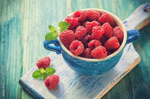 Fresh organic raspberries on the blue wooden background - 275072968