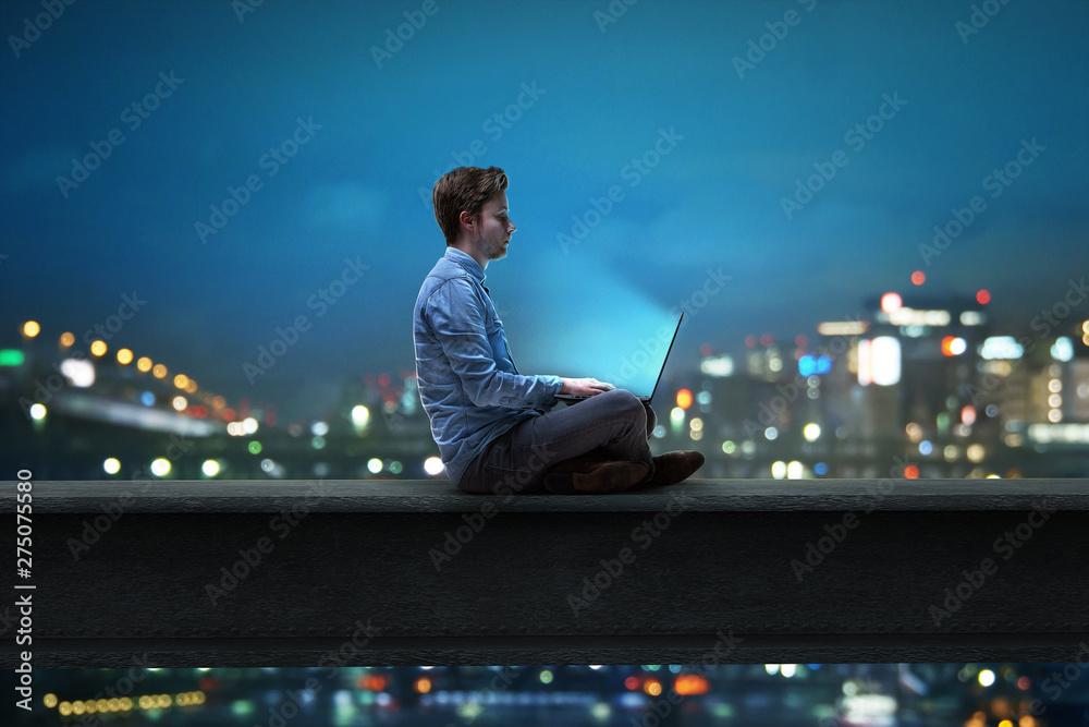 Fototapeta Mann sitzt am Notebook vor nächtlicher Stadt