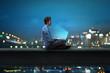 canvas print picture - Mann sitzt am Notebook vor nächtlicher Stadt