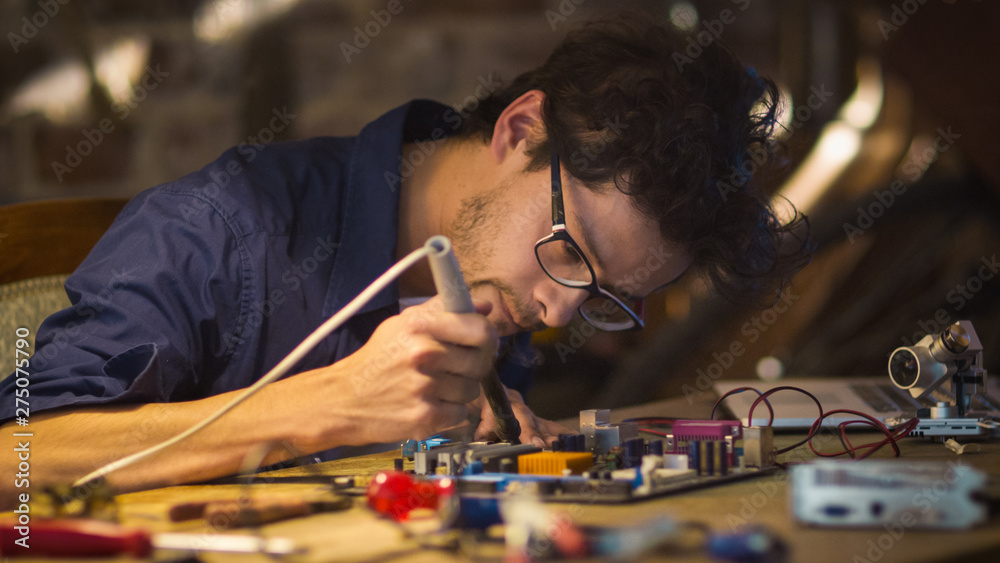 Fototapety, obrazy: Student is studying electronics and soldering a circuit board in a garage.