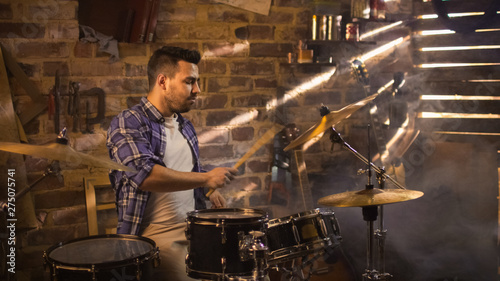 Drummer plays music while rehearsing a song in a home studio in a garage. - 275075741
