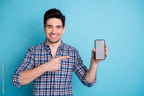 Photo portrait of confident positive optimistic cheerful with beaming toothy smile agent salesman trader freelancer businessman holding cellular in hand arm isolated pastel background