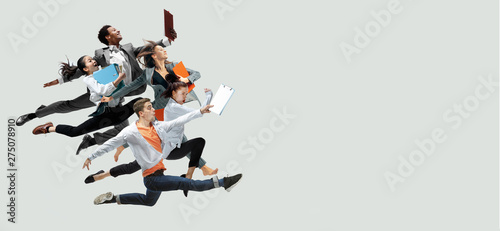 Photo  Happy office workers jumping and dancing in casual clothes or suit with folders isolated on studio background