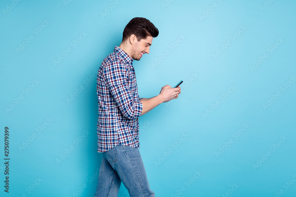 Fototapety, obrazy: Photo portrait of careless positive optimistic handsome millennial holding using telephone while having a walk isolated pastel background