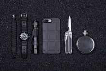 Everyday Carry (EDC) Military Items For Men- Multi Tool, Lighter, Mobile Phone In Protect Case, Tactical Watch, Survival Bracelet,flashlight And Flask Black Stone (minerals) Crumb Background.