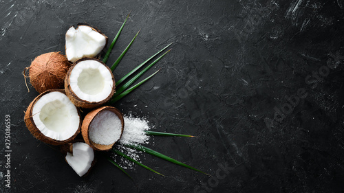 Coconut with palm leaves on a black stone background. Tropical Fruits. Nut. Top view. Free space for your text.