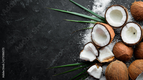 Stampa su Tela Coconut with palm leaves on a black stone background