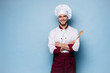 canvas print picture - Portrait of positive toothy chef cook in beret, white outfit having tools in crossed arms looking at camera.