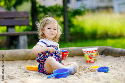 Obraz na plátně Cute toddler girl playing in sand on outdoor playground