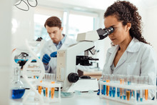 Smart Female Biologist Looking Into The Microscope
