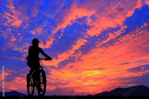 Foto auf Leinwand Koralle Silhouette man and bike relaxing on blurry sunrise sky background.