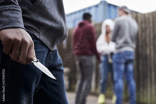 Foto Close Up Of  Teenage Boy In Urban Gang Holding Knife