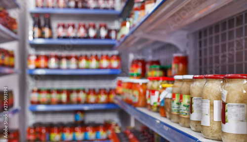 Fotografia  Different pickle goods at shelves in food store